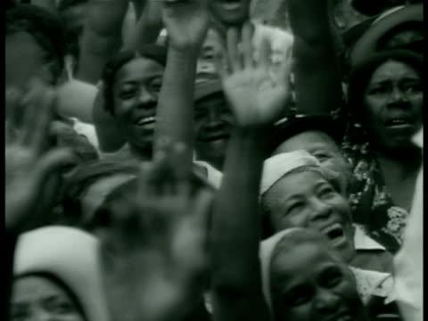 supporters standing on sidewalk waving, african american spiritual leader father divine waving from window of building. father divine sitting in... - atmosfär råmaterial bildbanksvideor och videomaterial från bakom kulisserna