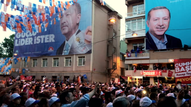 Supporters wave flags and cheer as they listen to Turkey's President Recep Tayyip Erdogan speak during a AK Parti election rally in Eyup on June 23...