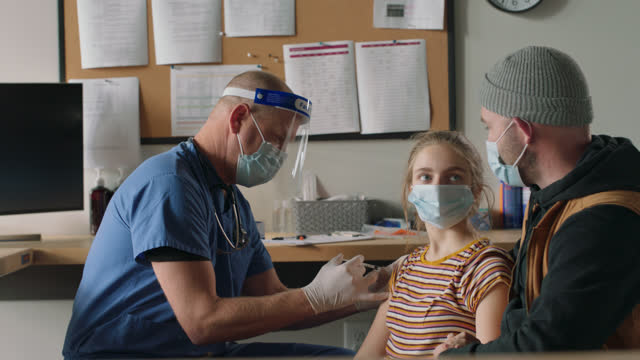 supportive father holds his daughter's hand as the doctor gives her the covid-19 vaccine - frontline worker stock videos & royalty-free footage