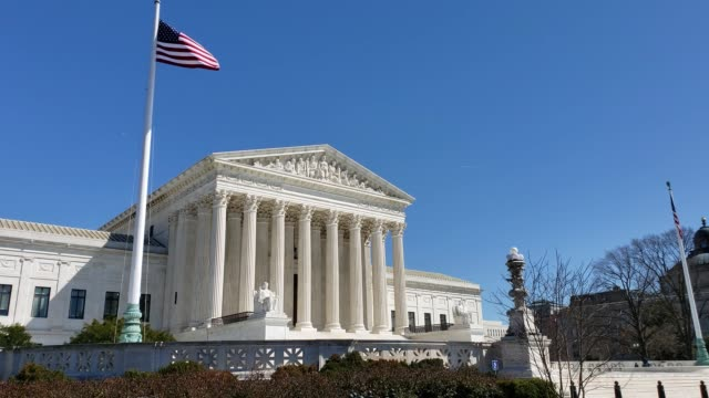 supreme court of the united states and american flag in washington, dc - oberstes bundesgericht der usa stock-videos und b-roll-filmmaterial