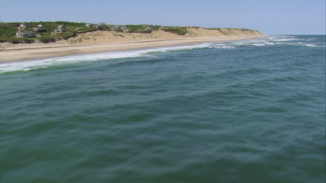 AERIAL Surf breaking on isolated sandy coastline and small community by the shore / Nantucket, Massachusetts, United States