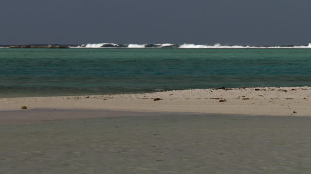 Surf breaks onto reef beyond sand bar and lagoon, Rangiroa, French Polynesia