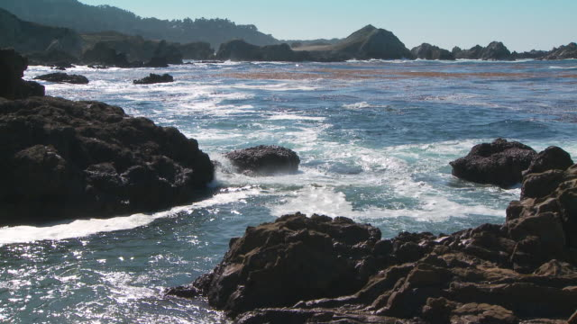 surf crashing against rocky shoreline and small inlet - inlet stock videos & royalty-free footage