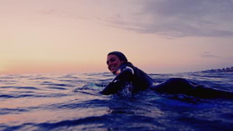 vídeos y material grabado en eventos de stock de chica surf paletas por cámara y salpica agua en la tabla de surf en un verano de california noche rodada en cámara lenta al atardecer. - surf