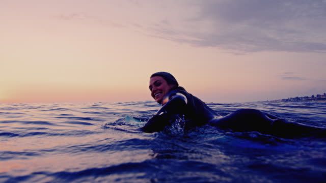 vídeos de stock e filmes b-roll de surf girl paddles by camera and splashes water while on surfboard on a california summer night shot in slow motion at sunset. - rebentação