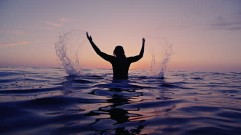 stockvideo's en b-roll-footage met surf meisje spatten water op een avond californië zittend op de surfplank beschoten zonsondergang in slow motion. - surf