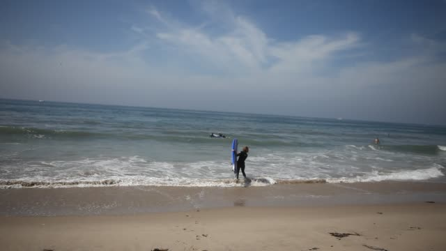 A surf instructor explains tourists from Germany during their first surf lessons on the beach of Venice Beach in Los Angeles California USA how to...
