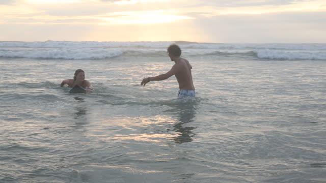 stockvideo's en b-roll-footage met surf instructor teaches young woman surfing basics, in surf - ecuadoriaanse etniciteit