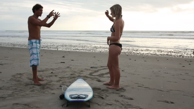 surf instructor teaches young woman surfing basics, on beach - instructor stock videos & royalty-free footage
