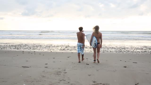 stockvideo's en b-roll-footage met surf instructor teaches young woman surfing basics, on beach - ecuadoriaanse etniciteit