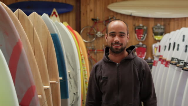 surf shop owner standing between two rows of surfboards in shop - 物の集まり点の映像素材/bロール