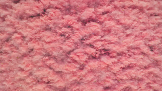 vídeos de stock e filmes b-roll de a surface filled with blush pink colored powder blasting towards camera and making smoky texture in close up and super slow motion - amor