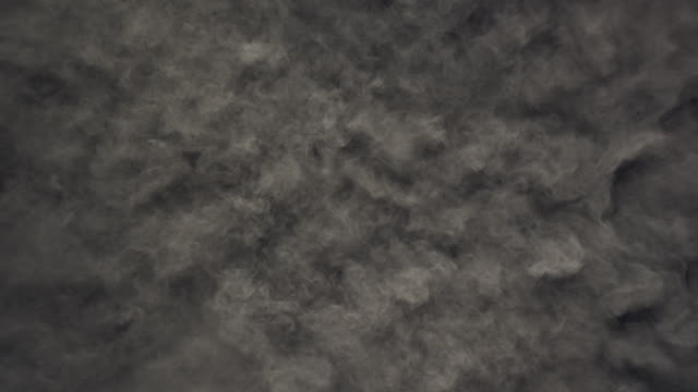 a surface filled with charcoal grey colored powder blasting towards camera and bouncing smoky texture in close up and super slow motion - black colour stock videos & royalty-free footage