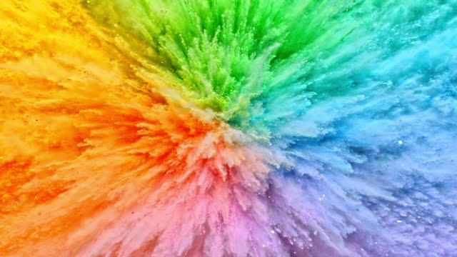 vídeos de stock e filmes b-roll de a surface filled with colorful powder blasting towards camera and making smoky texture in close up and super slow motion - colorido
