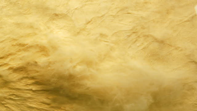 a surface filled with golden powder foundation blowing out of frame and making smoky texture in close up and slow motion - toned image stock videos & royalty-free footage