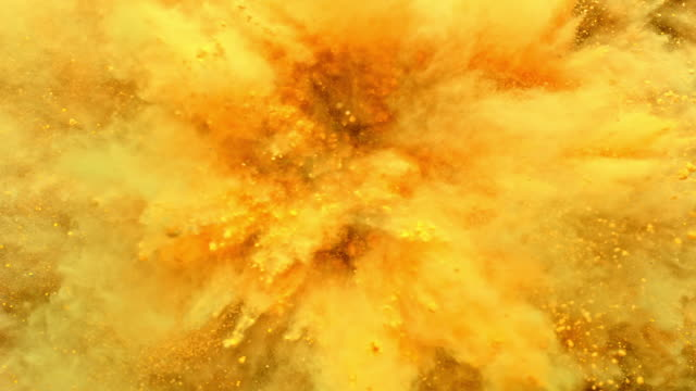 a surface filled with orange yellow colored powder blasting towards camera and making smoky texture in close up and super slow motion - gelb stock-videos und b-roll-filmmaterial