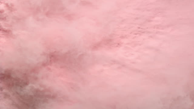 a surface filled with pink colored powder foundation blowing out of frame and making smoky texture in close up and slow motion - blowing stock videos & royalty-free footage