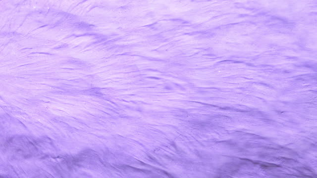 vidéos et rushes de a surface filled with purple sand colored powder foundation blowing out of frame and making smoky texture in close up and slow motion - art