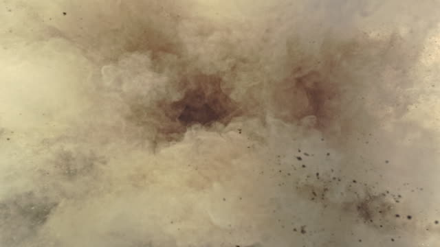 a surface filled with sand colored powder foundation blasting towards camera and making smoky texture in close up and super slow motion - terreno video stock e b–roll