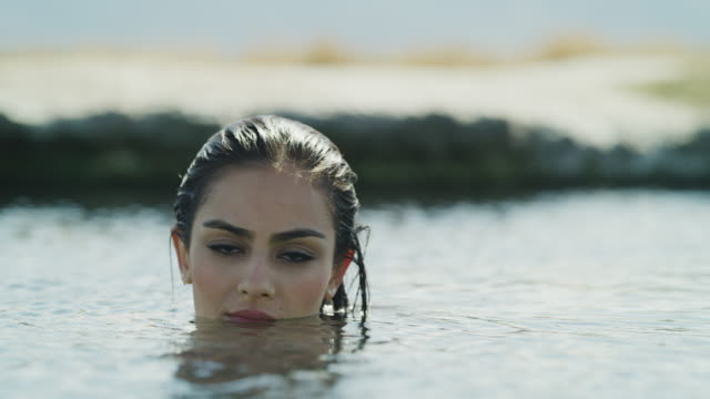 surface level close up of face of woman floating in natural pool and turning to camera / meadow, utah, united states - floating on water stock videos & royalty-free footage