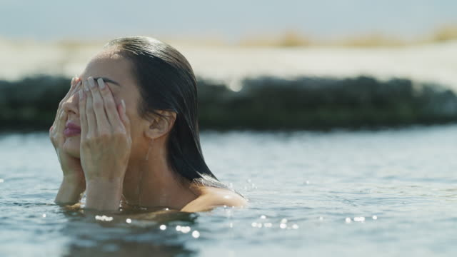 Surface level close up of woman surfacing in natural pool and wiping eyes / Meadow, Utah, United States