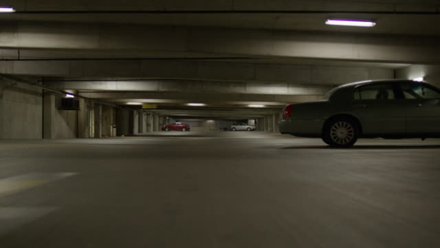 vídeos de stock e filmes b-roll de surface level panning shot of cars in parking garage / provo, utah, united states - dolly shot