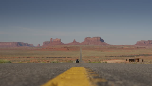 surface level view of approaching motorcycles in scenic landscape / monument valley, utah, united states - low angle view stock videos & royalty-free footage