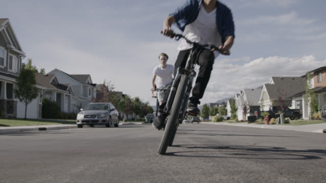 surface level view of boys riding bicycles passing on suburban street / lehi, utah, united states - lehi stock videos & royalty-free footage