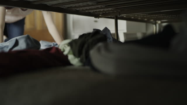 vidéos et rushes de surface level view of girl searching for clothing on floor underneath bed / cedar hills, utah, united states - sale