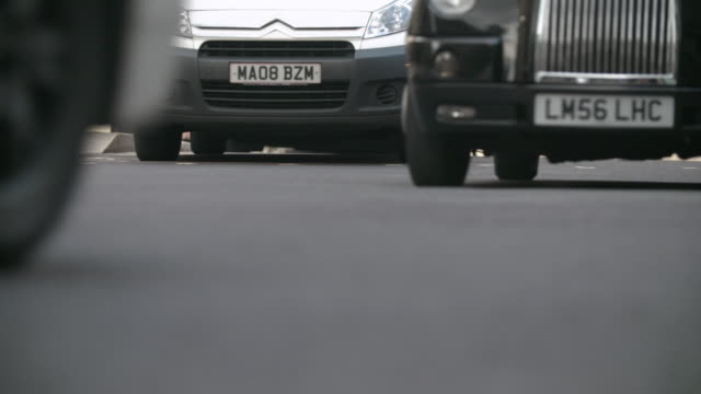 slo mo cu selective focus surface level view of traffic passing street / london, england, united kingdom - traffic点の映像素材/bロール