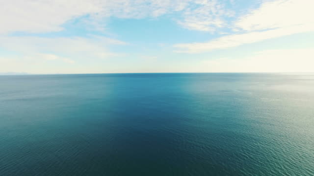 AERIAL: Surface of the blue sea in morning light