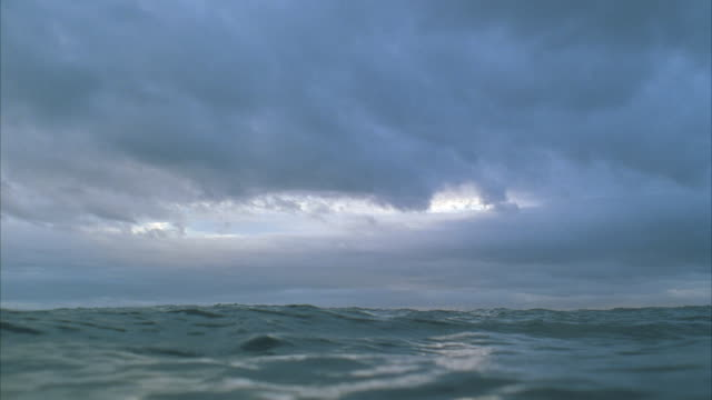 pov ws surface view of sun setting over sea horizon - underwater stock videos & royalty-free footage