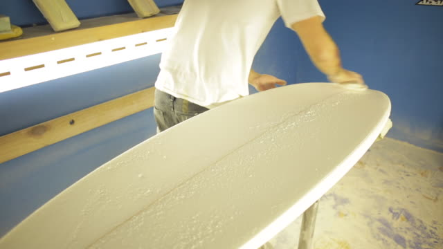 Surfboard blank being hand sanded.