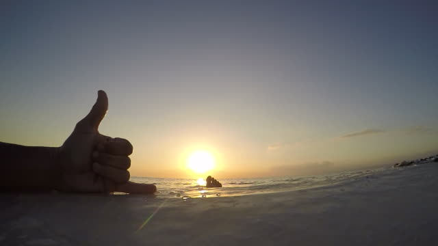 a surfboard in the sea at sunset and a surfer making a friendly shaka hand gesture. - slow motion - mit handkamera stock-videos und b-roll-filmmaterial