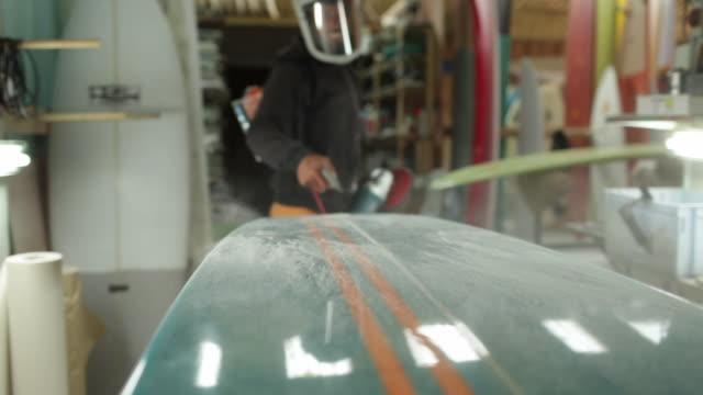 surfboard shaper blowing fibreglass dust off of surfboard surface - fibreglass stock videos and b-roll footage