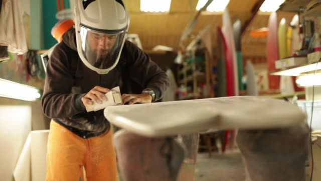 Surfboard shaper sanding surface of surfboard with sand paper