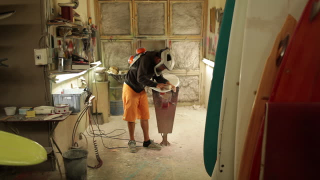 Surfboard shaper sanding surface of surfboard with sandpaper