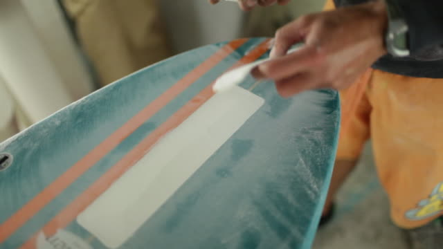 Surfboard shaper touching and sanding newly finished surface of surfboard