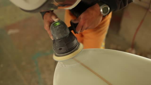 Surfboard shaper working on sanding surfboard