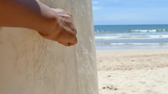 stockvideo's en b-roll-footage met surfer wax toe te passen op een surf - lycra