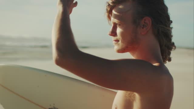 vídeos de stock, filmes e b-roll de surfista na praia - traje de mergulho