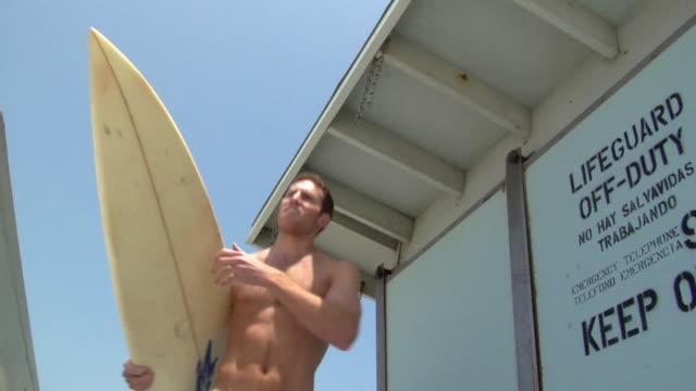 vídeos y material grabado en eventos de stock de slo mo ms la surfer carrying board / manhattan beach, california, usa - marrón
