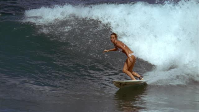 A surfer catches a wave and performs tricks on it until she wipes out.