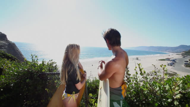surfer couple looking down to sea from above - bikinihose stock-videos und b-roll-filmmaterial