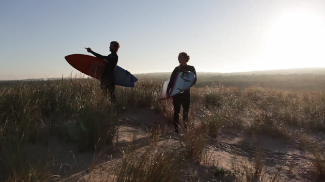 Surfer couple pointing toward surf break on dune with surfboards in morning in South of France