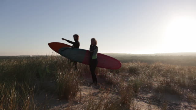 surfer couple pointing toward surf break on dune with surfboards in morning in south of france - pointing finger stock videos and b-roll footage