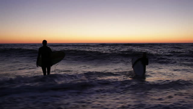 Surfer couple walking out of ocean with surfboards after evening surf