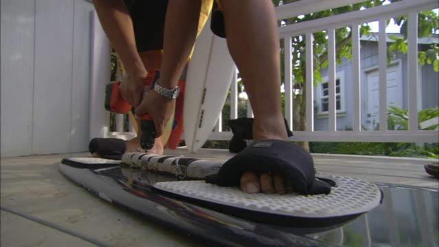 a surfer detaches a line of padding from his board. - sportschützer stock-videos und b-roll-filmmaterial