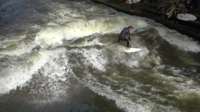ms surfer enjoying surfing at eisbach river in englischer garten park / munich, bavaria, germany - ミュンヘン エングリッシャーガルテン点の映像素材/bロール