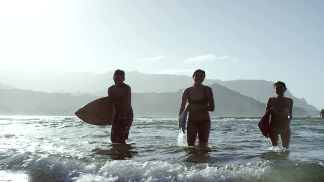 Surfer friends walking on the beach in Hawaii